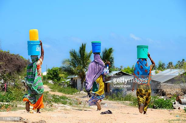 african women go to fetch water w/ buckets on head - zanzibar island stock photos and pictures