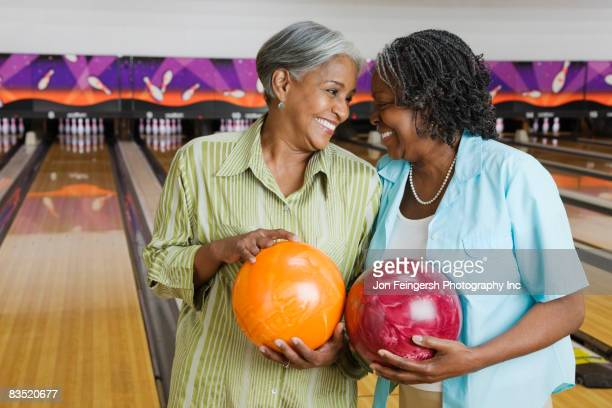 african women holding bowling balls in bowling alley - black alley stock photos and pictures