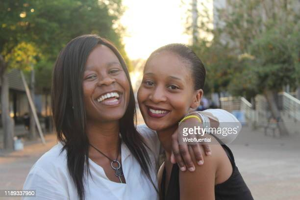 african women hugging in the street - webfluential stock pictures, royalty-free photos & images