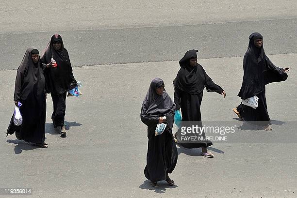 African women living in Saudi Arabia carry their belongings as they wait to cross a main street in the Red Sea city of Jeddah on July 7 2011 AFP...