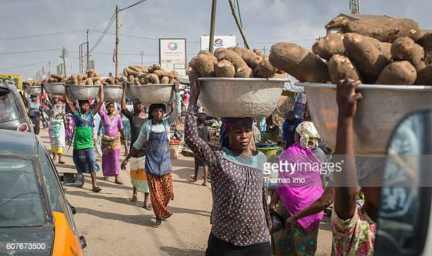 African women transport potatoes on their heads on the market in Agbogbloshie a district in Ghana's capital on September 09 2016 in Accra Ghana