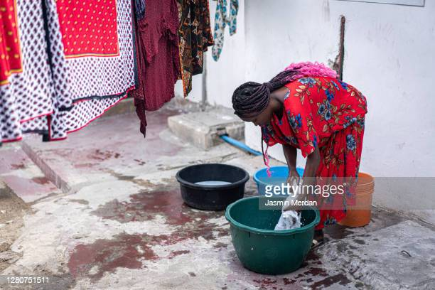 african women washing clothes outdoors in plastic buckets - condition stock pictures, royalty-free photos & images