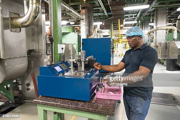 African worker operating quality control machine in aluminium can factory