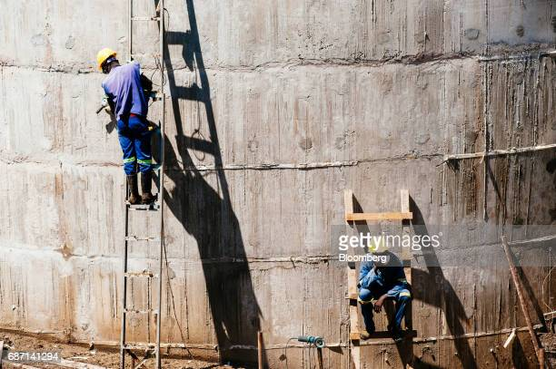 African workers stand on ladders at the construction site for a hydro pumping station which will supply water from the Limpopo river to nearby rice...
