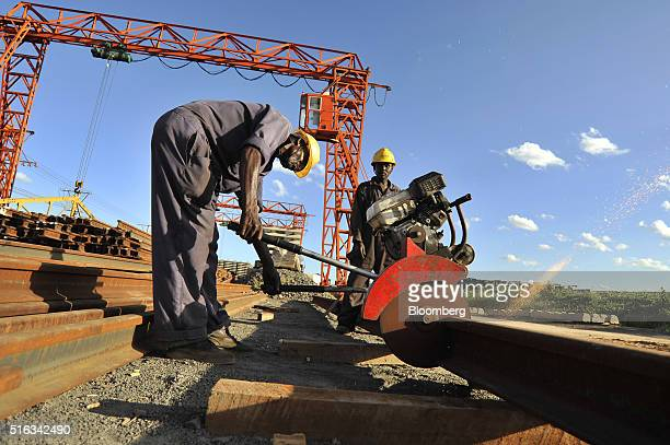 African workers use a circular saw to cut a length of steel rail track at the Kathekani Tgirder and rail sleeper manufacturing plant which makes...