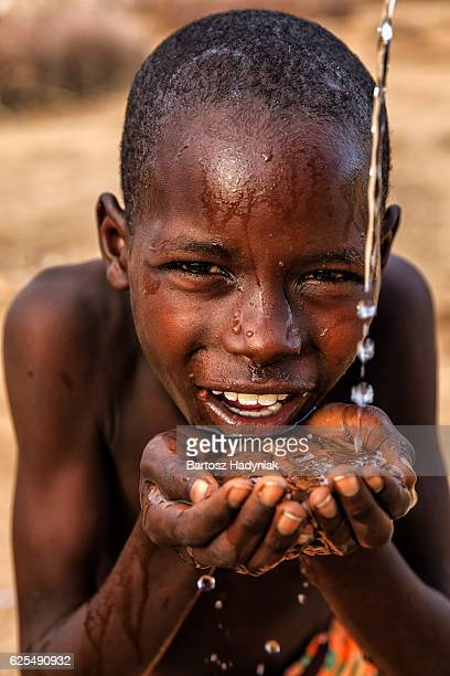 African young boy beber agua fresca on savanna, África Oriental
