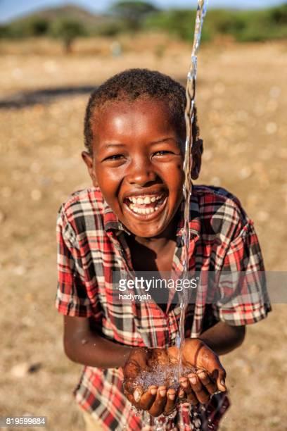Afrikanische junge trinkt Wasser auf Savanne, Osten und Afrika