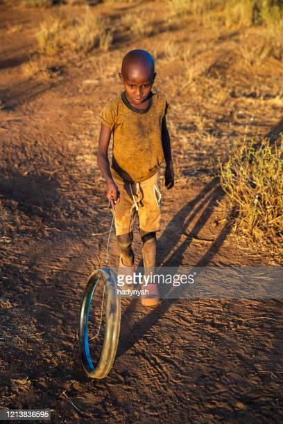 afrikaans jonge jongensspel met een wiel op savanne, oost-afrika - african tribal culture stockfoto's en -beelden