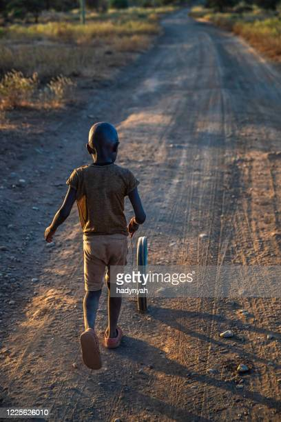 african young boy play with a wheel on savanna, east africa - native african girls stock pictures, royalty-free photos & images