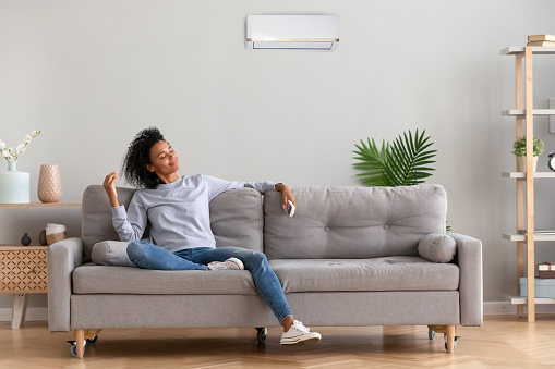 African young relaxed woman sitting on couch breathing fresh air 1133045032