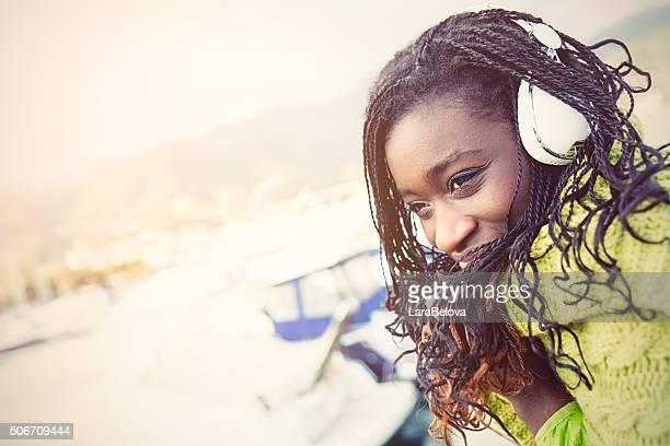 Afrikanische junge Frau, die Musik hören im Freien