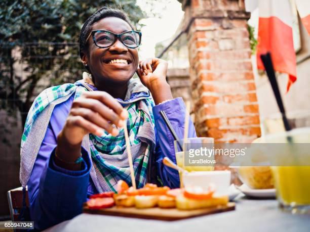 Junge Afrikanerin mit Aperitif im Straßencafé