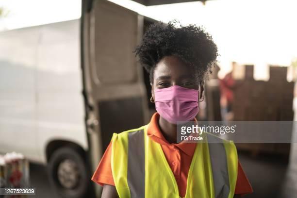 afrikanische junge frau porträt in lagerhaus mit gesichtsmaske - essenzielle berufe und dienstleistungen stock-fotos und bilder