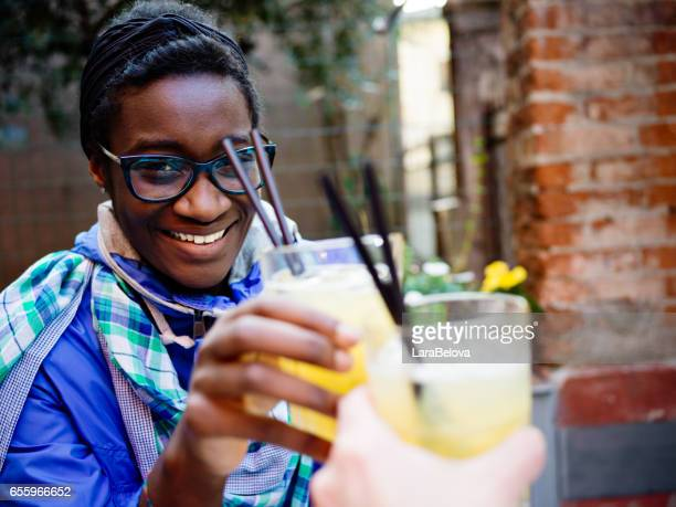 African young woman with cocktail in sidewalk cafe
