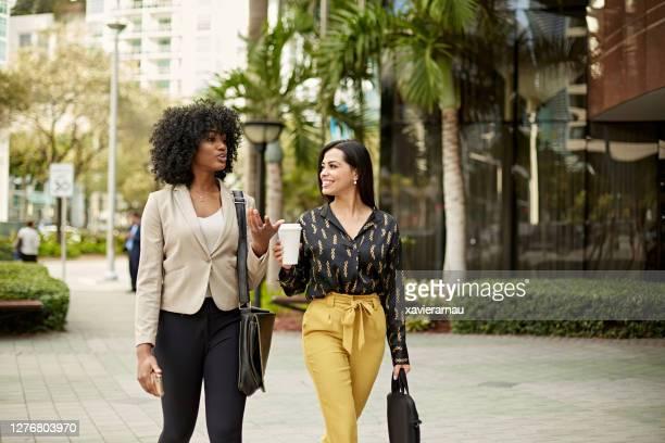 アウトドアを歩くアフリカ系アメリカ人とヒスパニック系のビジネスウーマン - 接近する 女性 ストックフォトと画像