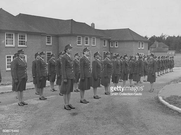 AfricanAmerican Army nurses standing at attention in front of their barracks and being inspected by staff officers Army nurse training center England...