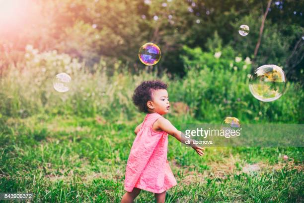 african-american baby girl playing with soap bubbles in the park - baby girls stock pictures, royalty-free photos & images