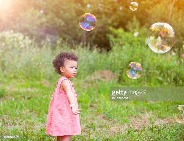 African-American baby girl playing with soap bubbles in the park
