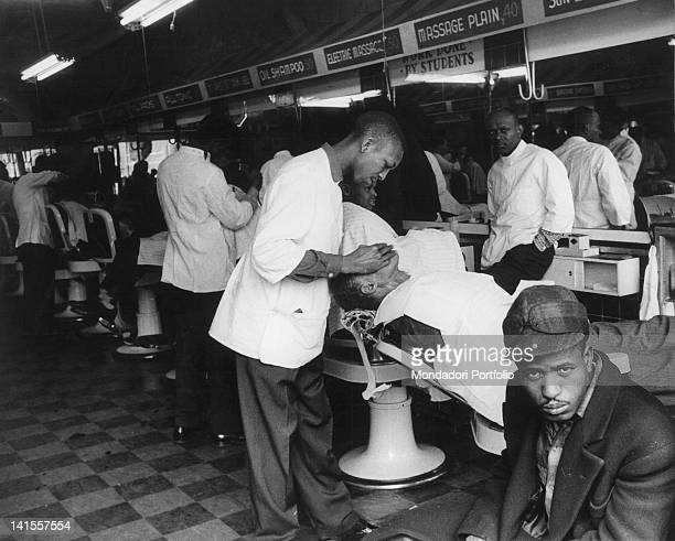 AfroAmerican barbers working in a men's barber shop in Harlem New York February 1956
