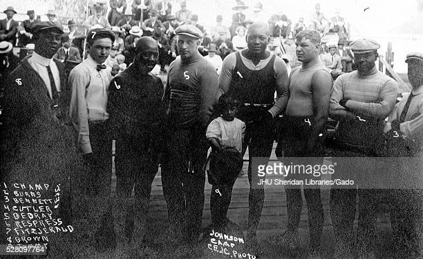 AfricanAmerican boxer Jack Johnson standing with a group of boxers and a young boy 1912