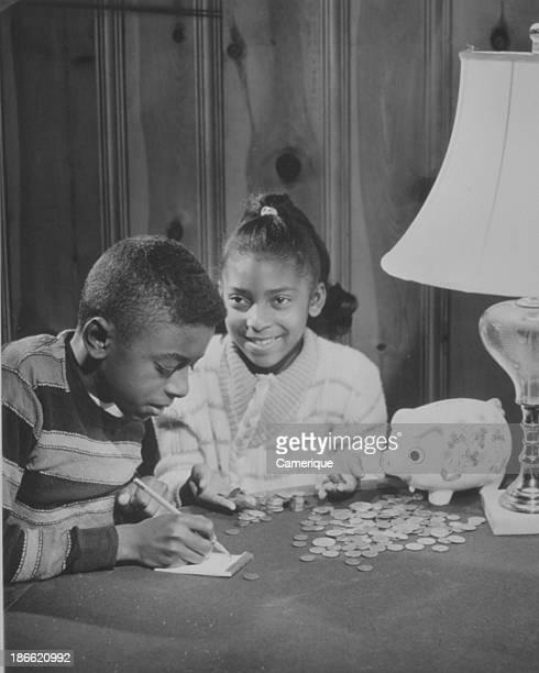 AfricanAmerican boy and girl adding up their money from their piggybank Locustville VA July 16 1966