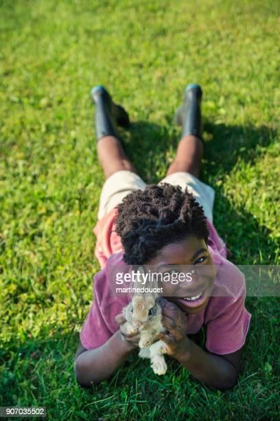 African-american boy cuddling baby rabbit outdoors in spring.