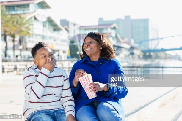 african-american boy,  grandmother in city eating popcorn - city_(florida) stock pictures, royalty-free photos & images