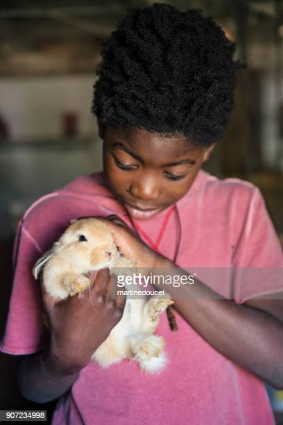 African-american boy holding a baby rabbit in an old barn.