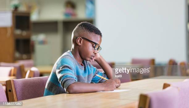 african-american boy in elementary school, writing - one boy only stock pictures, royalty-free photos & images