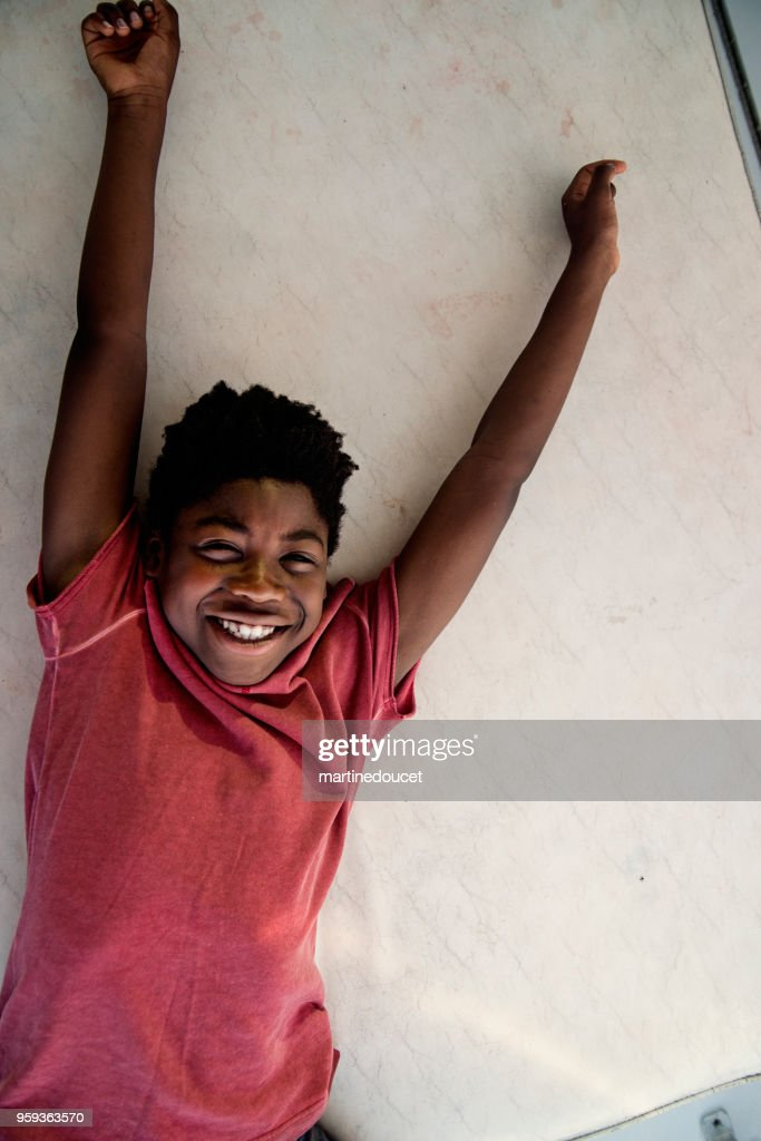 African-american boy lying down in a boat. : Stock Photo
