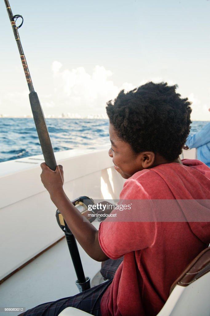 Chico afroamericano en un viaje de pesca de mar. : Foto de stock