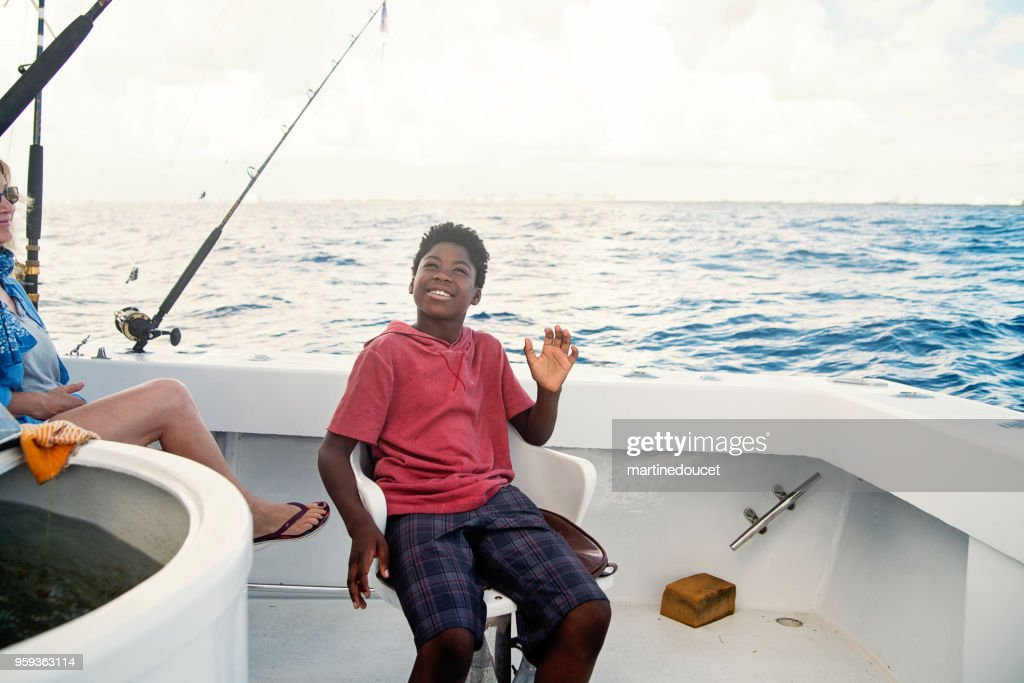 African-american boy on a sea fishing trip. : Stock Photo
