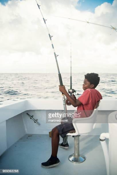 African-american boy on a sea fishing trip.