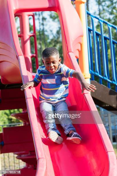 african-american boy on playground slide - sliding stock pictures, royalty-free photos & images