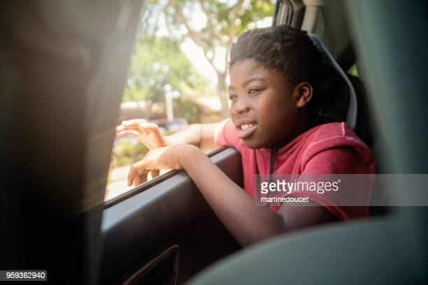 African-american boy on the back seat of a car.