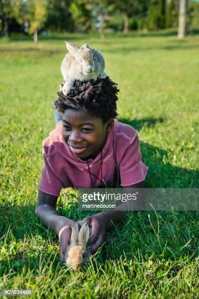 african-american boy playing with baby rabbits outdoors in spring. - african american easter stock photos and pictures
