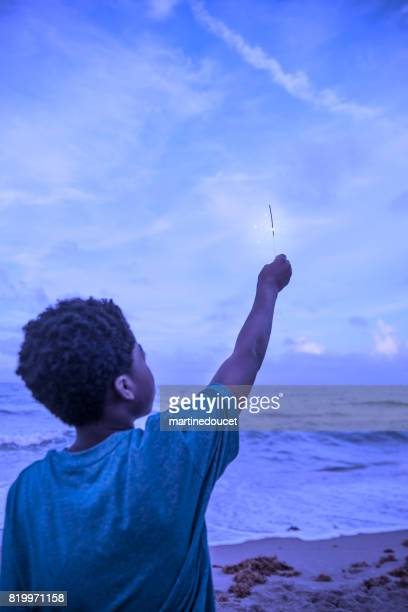 African-american boy playing with sparklers on the beach at dusk.