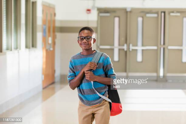 afroamerikanischer junge steht im schulflur - schulkind nur jungen stock-fotos und bilder