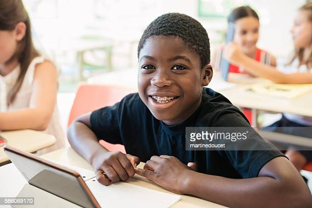 African-american boy using electronic tablet in classroom.