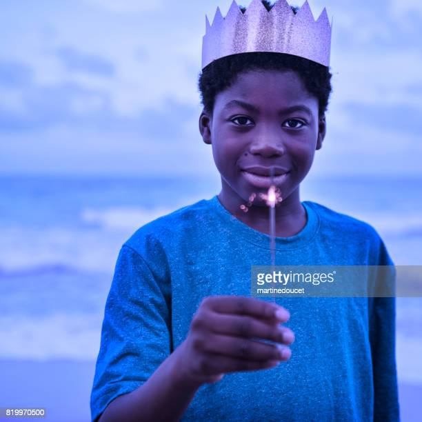 African-american boy with a crown and sparklers on the beach at dusk.