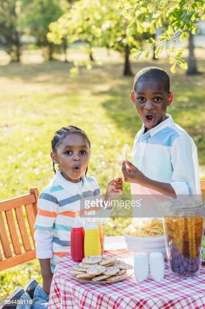 african-american brothers eating potato chips - caught in the act stock pictures, royalty-free photos & images