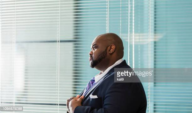 African-American businessman with large build, frowning