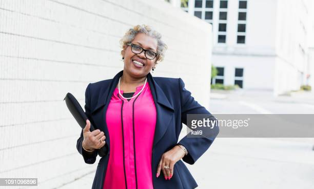 African-American businesswoman in city, hand on hip