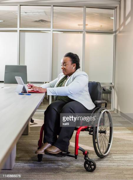 african-american businesswoman in wheelchair uses tablet - of deformed people stock pictures, royalty-free photos & images