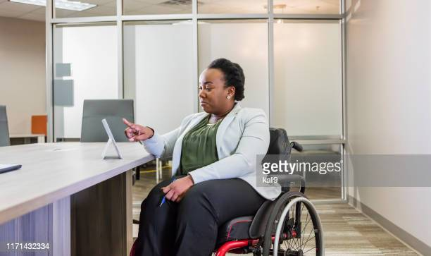 african-american businesswoman in wheelchair uses tablet - persons with disabilities stock pictures, royalty-free photos & images