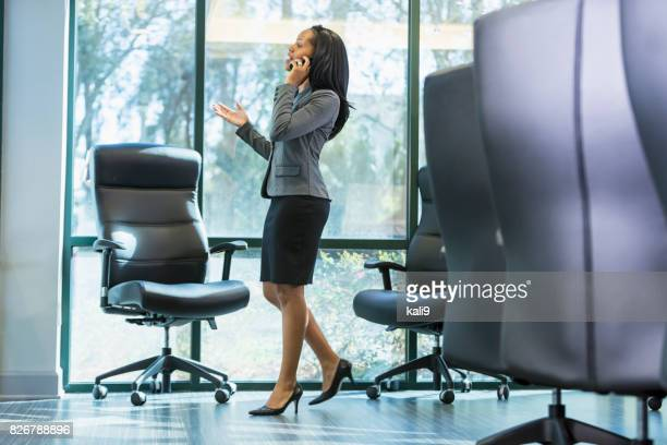 african-american businesswoman talking on phone - black skirt stock pictures, royalty-free photos & images