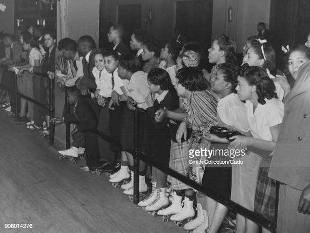 AfricanAmerican children wearing roller skates leaning on railing during entertainment event Chicago Illinois USA 1935 From the New York Public...