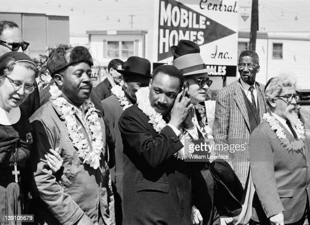 AfricanAmerican civil rights activist Martin Luther King Jr listening to a transistor radio in the front line of the third march from Selma to...