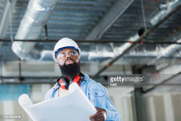 african-american construction worker with plans - building contractor stock pictures, royalty-free photos & images