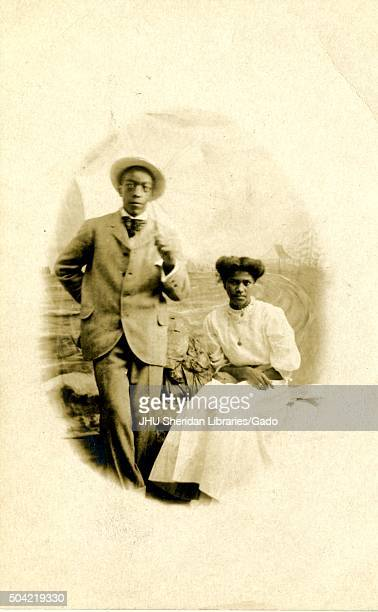 AfricanAmerican couple a man and a woman posing for a studio portrait against a painted backdrop the man wearing a suit and straw hat and standing...